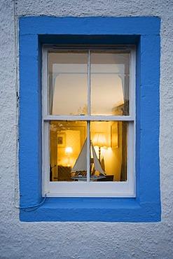 Illuminated window with miniature sailboat, Scotland, United Kingdom, Europe