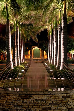 Illuminated Palm Avenue and fountain in front of the harbourmaster, Frederiksted, island of St. Croix, U.S. Virgin Islands, USA