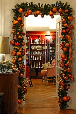 Doorway decorated with pine branches and Christmas baubles, view to a display cabinet with silverware, Villa & Ambiente store, Im Weller, Nuremberg, Middle Franconia, Bavaria, Germany, Europe