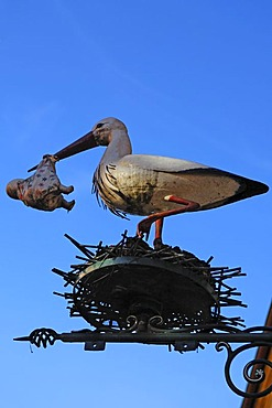 Stork with baby figure in its beak above a children's shop, Obere Bruecke, Bamberg, Upper Franconia, Bavaria, Germany, Europe
