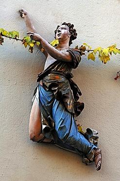 Colored wooden carved figure on a building facade, Karolinenstrasse, Bamberg, Upper Franconia, Bavaria, Germany, Europe