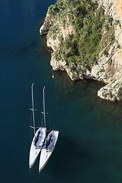 Two sailboats lying in the port of Fontvieille against the rocks of the old town, Principality of Monaco, the Cote d'Azur, Europe