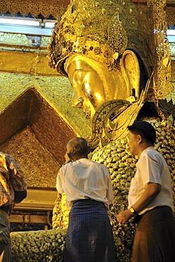 Believers sticking gold foil on a Buddha statue, Mahamuni Pagoda, Mandalay, Burma, Myanmar, Southeast Asia