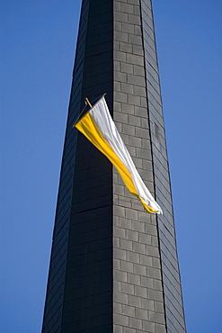 White and yellow flag fluttering from a church tower window against a steel blue sky