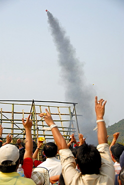Rocket rising in the sky shortly after launch from a launch pad, cheering spectators, Pi Mai, Lao New Year festival, city of Phongsali, Phongsali province, Laos, Southeast Asia, Asia
