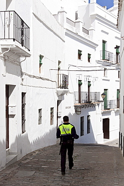 Spanish policeman of the Policia Local in a small alley in Vejer de la Frontera, Andalusia, Spain, Europe