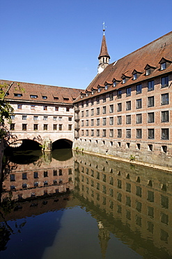 Public historic Heilig-Geist-Spital Holy Spirit hospital, retirement home, church tower, courtyard, arcades, reflection, old town, Nuremberg, Middle Franconia, Franconia, Bavaria, Germany, Europe