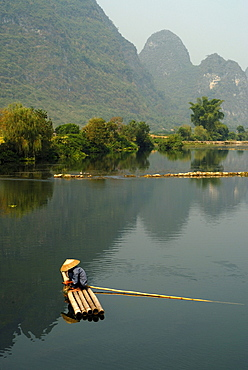 Chinese fisherman with a straw hat on a bamboo raft fishing near Yangshuo in the Yulong River in front of limestone cliffs, Yangshuo, Guilin, Guanxi, China