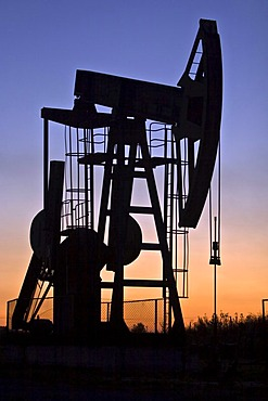 An industrial pumpjack in the sunset, silhouette