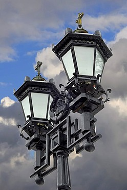 Two black iron lantern against the cloudy sky