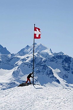 Swiss national flag and alpine sportspeople on the plateau Trais Fluors, St. Moritz, Oberengadin, Graubuenden, Switzerland