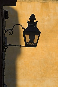 Silhouette of a street lamp in front of a yellow wall in Cordoba, Andalusia, Spain, Europe