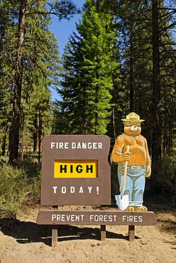Smokey Bear on a High Fire Danger warning sign in the National Forest, Oregon, USA