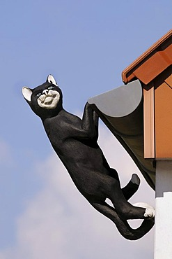 Black cat, sculpture, hanging from the gutter