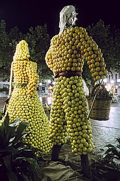Two figures made of citrus fruit, decorations for the Orange Festival, at night, Soller, Majorca, Balearic Islands, Spain, Europe