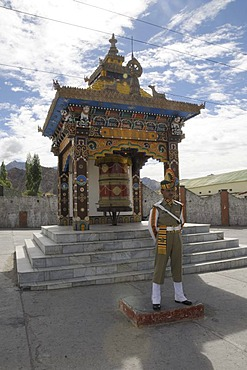 Indian soldier keeping watch in front of a Buddhist prayer wheel, Leh, Northern India, India, Himalayas