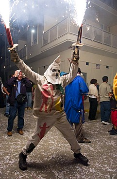 During the Correfoc or Fire Run, hooded Fire Devils run the streets of Spanish towns brandishing fireworks, Altea, Costa Blanca, Spain
