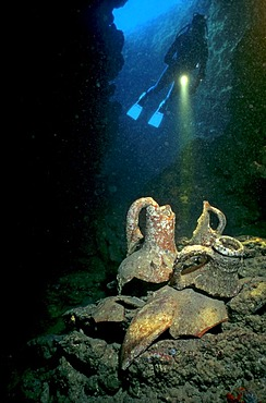 Scuba diver in an underwater cave with amphoras, Mediterranean Sea, Turkey