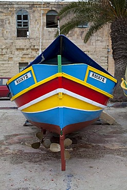 Traditional Maltese fishing boat, called Luzzu, standing ashore for maintenance, port of Marsaxlokk, Malta, Europe