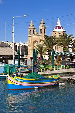 Traditional Maltese fishing boat, called Luzzu, in front of the Church of Our Lady of Pompeii, port of Marsaxlokk, Malta, Europe