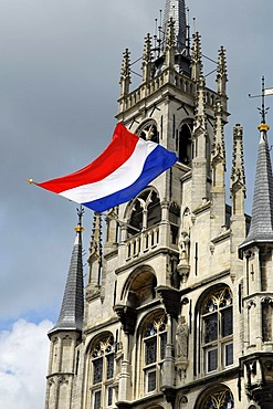 Gothic guildhall, stadhuis, on the marketplace of Gouda. The ensign indicates a nationwide celebration or commemoration day. Gouda, South-Holland, Zuid-Holland, Nederland, The Netherlands