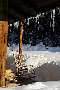 Old lodge with rocking chair, icicles, Dunton Hot Springs Lodge, Colorado, USA