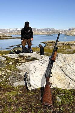 Trekker checking his shotgun for defence against polar bears, Ikasartivaq Fiord, East Greenland