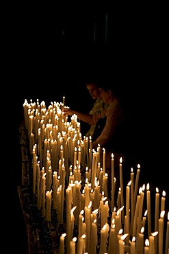 Young couple lighting votive candles in the Milan Cathedral, Duomo di Milano, Milan, Lombardy, Italy, Europe