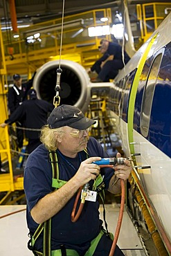 Worker does heavy maintenance on Embraer aircraft flown by American Eagle, Gwinn, Michigan, USA