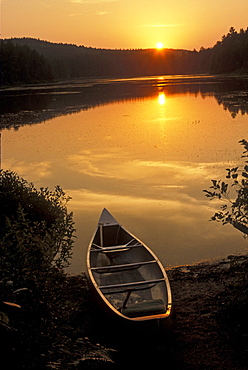 A canoe on the shore of the Barron River as the sun sets, Algonquin Provincial Park, Ontario, Canada, North America
