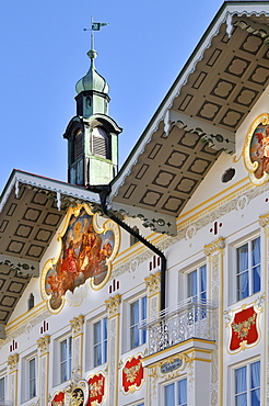 Building facade brightly painted (lueftlmalerei) beneath tower and weather vane, town hall, Bad Toelz, Bavaria, Germany