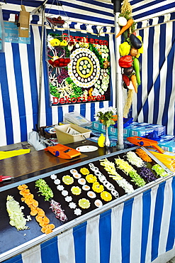Booth selling slices of various fruits and vegetables, Auer Dult Fair, Munich, Bavaria, Germany