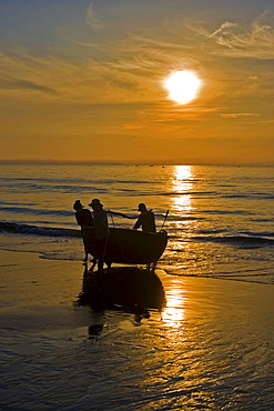 Vietnamese fishermen carrying their basket boat ashore, Mui Ne, Vietnam, Southeast Asia, Asia