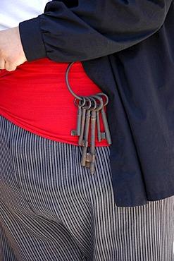 Bunch of keys with large keys hanging on the red sash of a large man, cummerbund