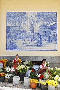 Woman selling flowers behind a azulejo (glazed tile) with a market scene, Funchal, Madeira, Portugal