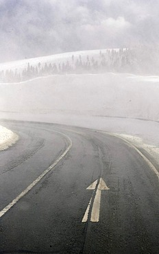 Wet lane and poor visibility in a curve on the road throug the Erzgebirge in winter, Erz Ore Mountains, Saxony, Germany