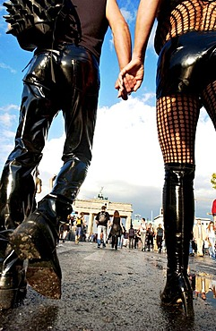 Fetish couple holding hands while walking to Brandenburg Gate during the Loveparade in Berlin, Germany