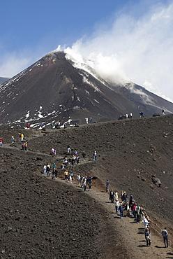Tourists hiking to Mt. Etna, smoke, Sicily, Italy