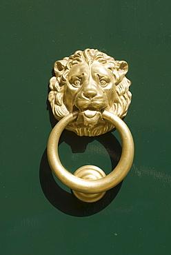 Lion head door knocker on a door in Polignano a Mare, Italy