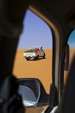 Glimpse out of the window of a vehicle to a pickup Toyota jeep Ubari Sand Sea Libya