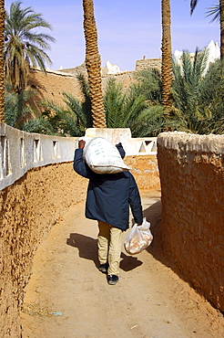Man returning from the market with heavy bags, Old town of Ghadames Libya