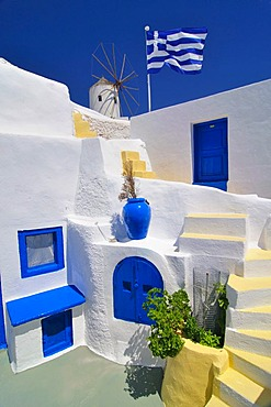 Blue and yellow inner courtyard with stairs, Greek flag blowing in the wind, typical Cycladic architecture, windmill behind, Oia, Ia, Santorini, Cyclades, Greece, Europe