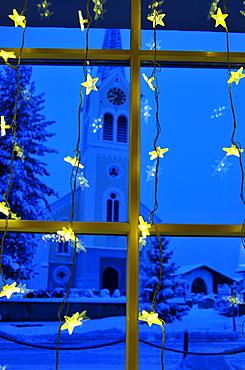 Christmas decoration, at the back the parish church Maria Opferung in Riezlern, Kleinwalsertal, Austria, Europe