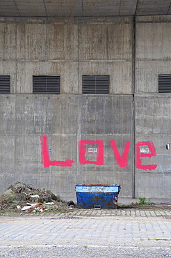 Container in front of a wall with the word love spray-painted in pink