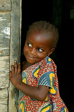 Young girl standing in the front door to her house, Cameroon, Africa