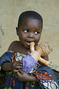 Young African girl holding a white doll, Cameroon, Africa