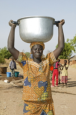 Woman carrying a pot of water on her head, well behind her, Pakete, Cameroon, Africa
