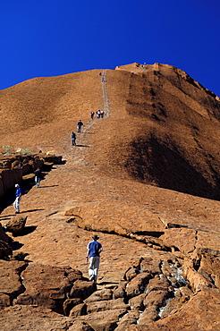 Tourists are climbing ayers rock, uluru, australia