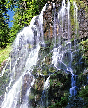 Waterfall in a mountain stream with moss-covered rocks. cascade