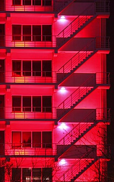 NLD, The Netherlands, Rotterdam: Fire escape stairs at a building, red illuminated. |